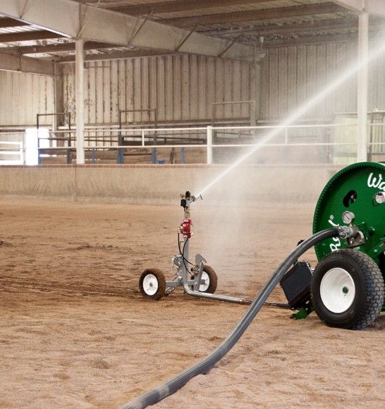 Using a water reel sprinkler to water an indoor arena